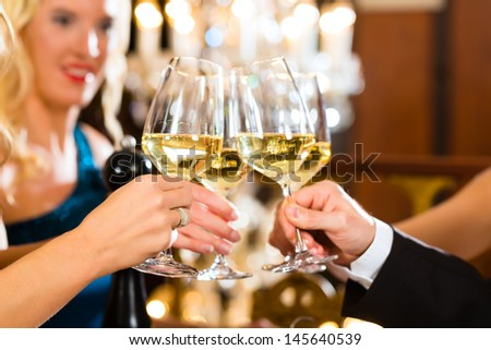 Good friends - man and women, drinking wine and clinking glasses in a fine dining restaurant, each with a glass in hand, a large chandelier is in Background - stock photo