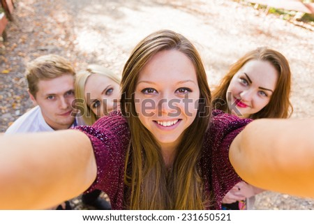 Good friends photobombing a young beautiful woman's selfie for social network. - stock photo