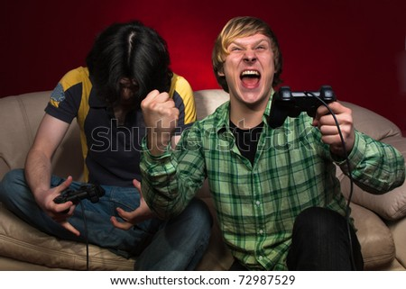 Good friends playing video games on a red background