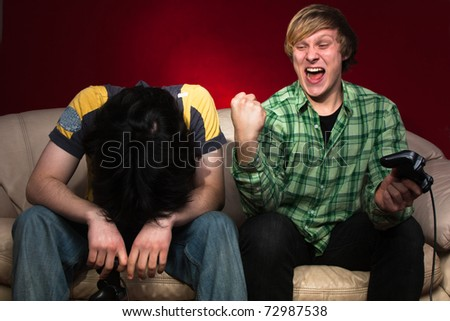 Good friends playing video games on a red background - stock photo