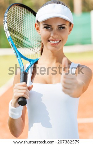 Good game! Beautiful young woman in sports clothing carrying tennis racket on shoulder and showing her thumb up while standing on court - stock photo