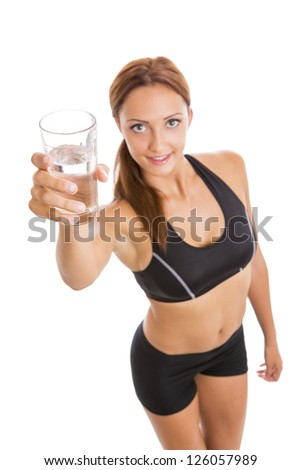 Good hydration - Portrait of beautiful smiling fitness woman holding up a glass of water over white background. Selective focus on water glass. - stock photo