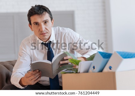 Good idea. Attentive clever young man sitting in a comfortable armchair and holding a notebook with important information while a box full of personal items standing by his side