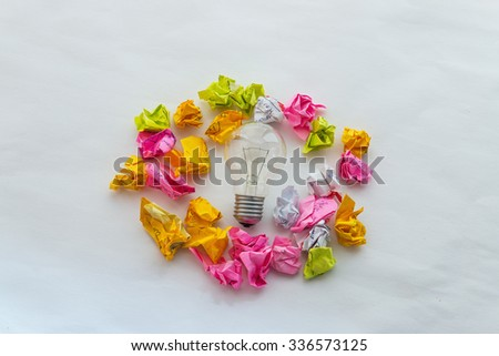 Good idea concept with crumpled colorful paper and light bulb on white background - stock photo