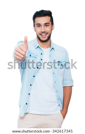 Good job! Happy young Indian man showing his thumb up and smiling while standing against white background - stock photo