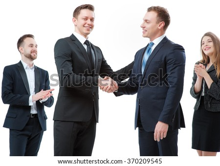 Good job! Partnership and congratulations.Two cheerful business men shaking hands while their colleagues applauding and smiling in the background. Isolated on white. - stock photo