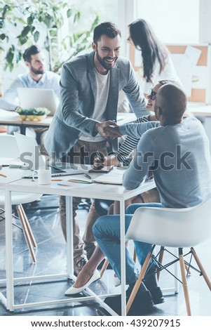 Good job! Two cheerful businessmen shaking hands while being in office together with their colleagues  - stock photo