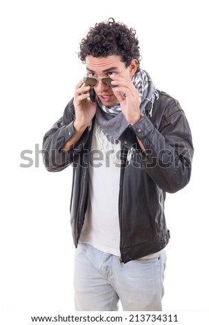 good looking adult man in a leather jacket talking over phone - stock photo