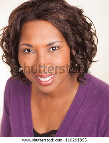 Good looking African American lady relaxing at home wearing purple sweater. - stock photo