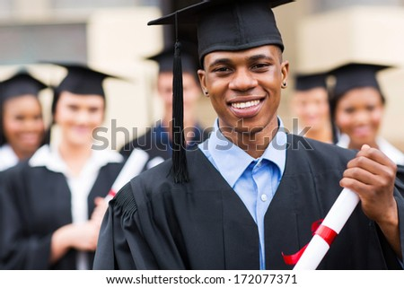 good looking african american male graduate in front of classmates - stock photo