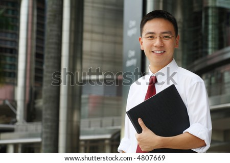 Good looking asian business man smiling with folder in hand. - stock photo