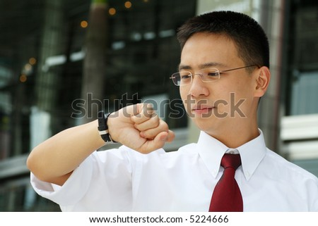 Good looking asian business man standing and looking at his watch for the time.