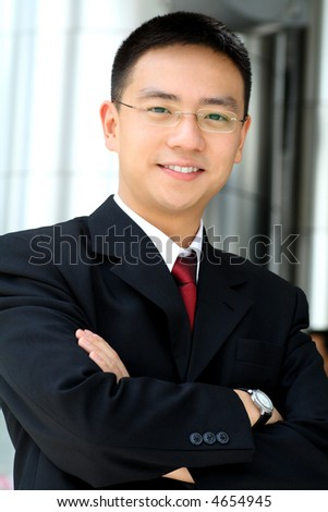 Good looking asian business man standing with arms folded.