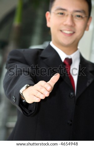 Good looking asian business man standing with arms outstretched ready to shake hands.
