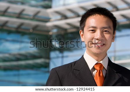 Good looking asian business man standing with formal suit. - stock photo