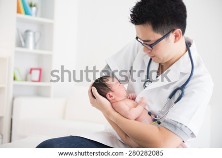 Good looking asian doctor and newborn baby on the clinic - stock photo