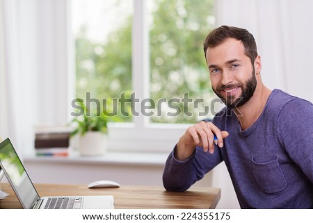 Good-looking bearded man in a home office sitting at a table with his laptop computer turning to smile at the camera - stock photo
