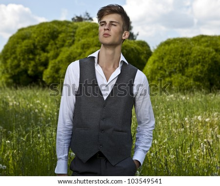 Good looking beautiful young man in classical suit pose outdoor - stock photo