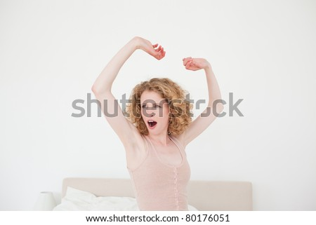 Good looking blonde female stretching in her bedroom in her apartment - stock photo