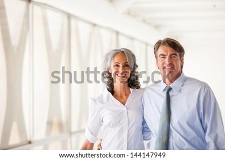 Good looking Business man and woman walking smiling at camera - stock photo