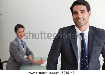 Good looking businessman posing while his colleague is working in an office - stock photo