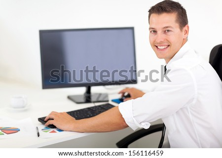 good looking businessman working on a computer in office - stock photo
