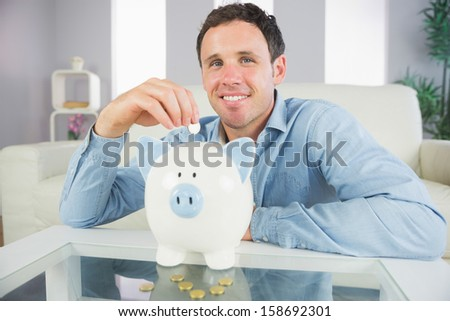 Good looking casual man putting coin in piggy bank in bright living room - stock photo