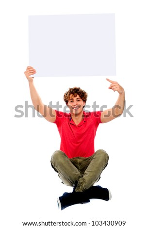 Good looking cool guy pointing towards white blank billboard, seated on floor - stock photo