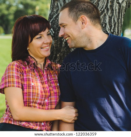 Good looking couple in love smiles each other outdoor