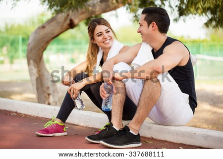 Good looking couple taking a break from their workout and flirting with each other - stock photo