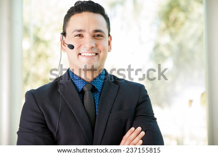 Good-looking customer service representative wearing a suit and a headset and speaking with a smile - stock photo