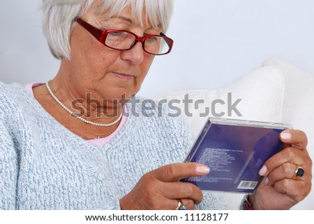 good looking elderly woman looking at compact disk