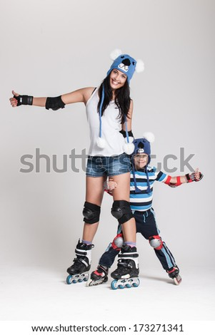 Good looking family, mother and son, posing in studio wearing inline rollerskates and matching funny hats - stock photo