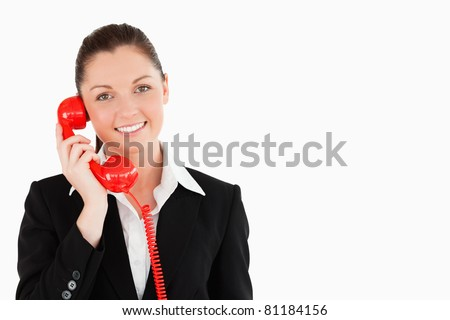Good looking female in suit on the phone while standing against a white background - stock photo