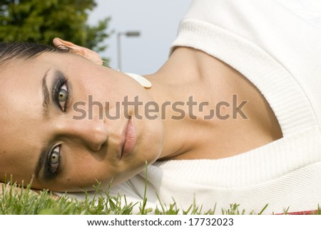 Good looking female laying in the grass looking at the camera - stock photo