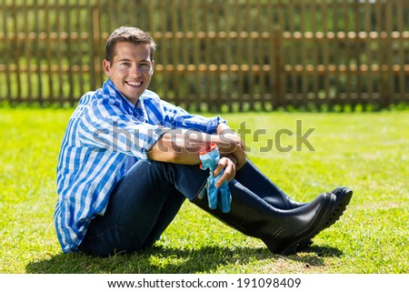 good looking gardener sitting on lawn - stock photo
