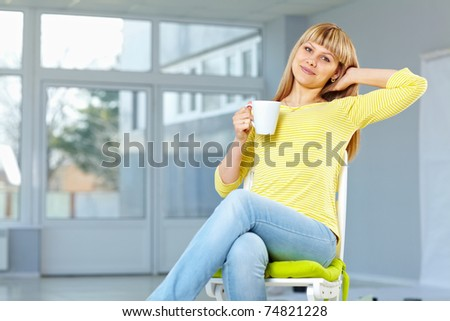 Good looking girl sitting on the chair and relaxing drinking something - stock photo