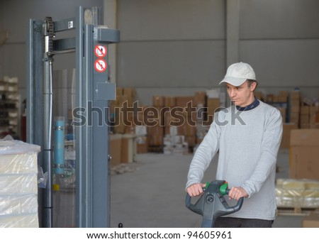 Good looking guy at forklift picking and moving packages in a warehouse - stock photo