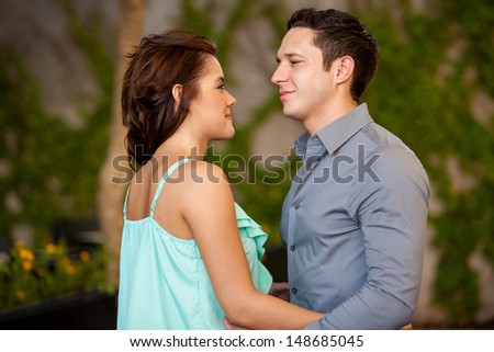 Good looking Hispanic couple looking at each other on a terrace - stock photo