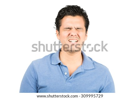 Good looking hispanic male in blue collared shirt eyes closed, grimacing with pained facial expression of suffering, pain, hurt and agony