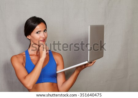Good-looking lady wearing tank top holding laptop with hand on chin while looking at camera on grey texture background