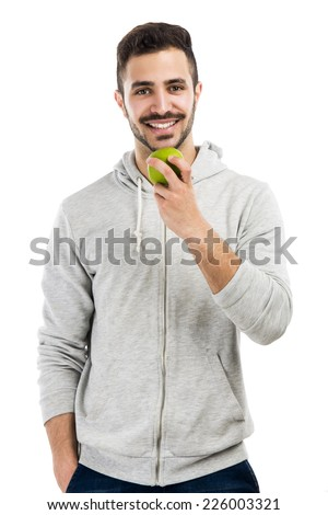 Good looking latin man eating a green apple, isolated on white background - stock photo