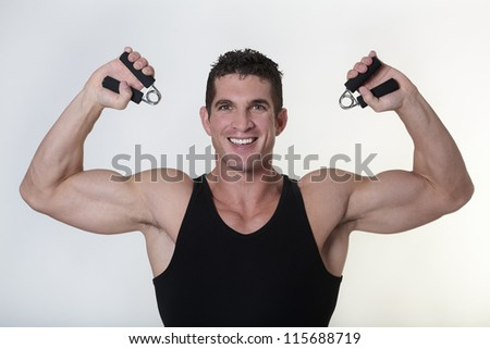 good looking male bodybuilder using hand gripper - stock photo