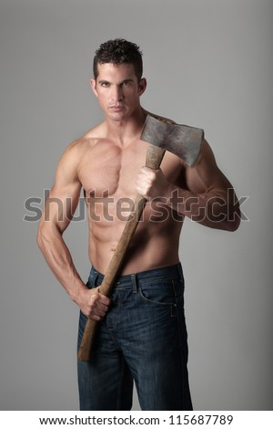 good looking male holding a well used axe to chop wood with - stock photo