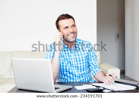 Good-looking man having a conversation on a mobile while paying his bills online - stock photo