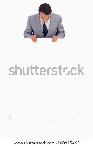 Good-looking man holding a big poster against white background