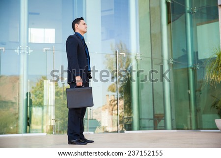Good-looking man in a suit and carrying a briefcase about to have a job interview - stock photo