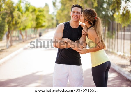 Good looking man in sporty outfit working out with his girlfriend and getting kissed in the cheek - stock photo