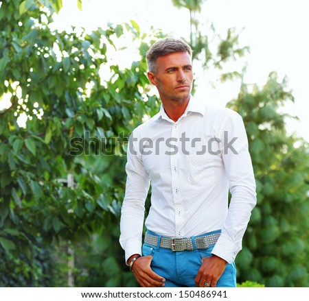 Good looking man outdoors with copy space - stock photo