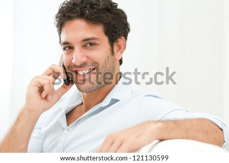 Good Looking Man Sitting On Sofa And Talking On Mobile Phone - stock photo